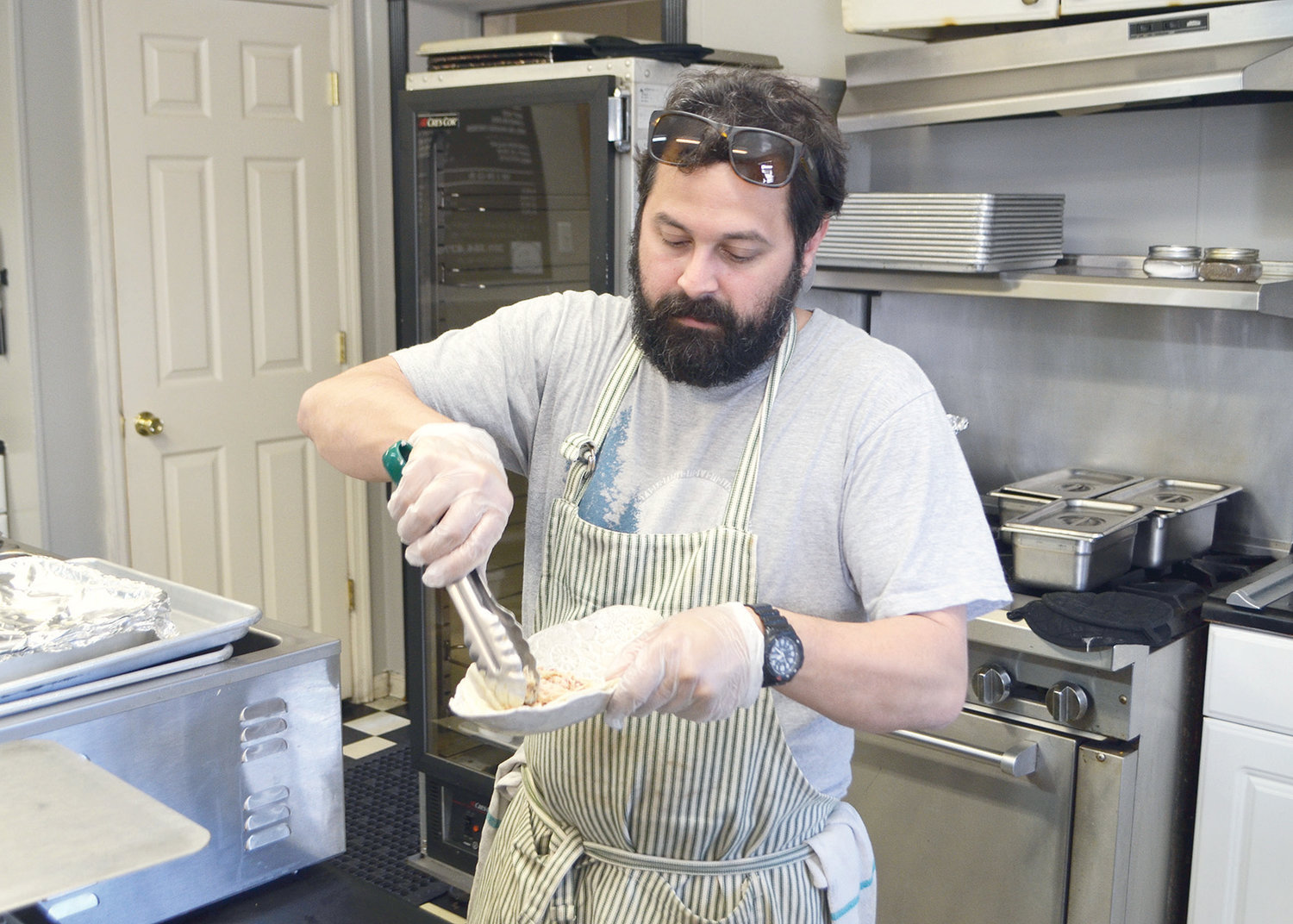 D's Downtown Barbecue owner Darren Hix prepares a dish at the restaurant.