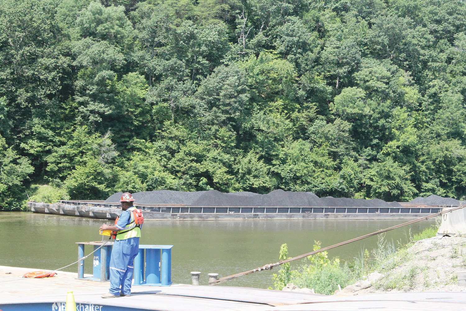 An Alabama Power employee is seen near a barge loaded with coal at Gorgas Steam Plant in 2014.