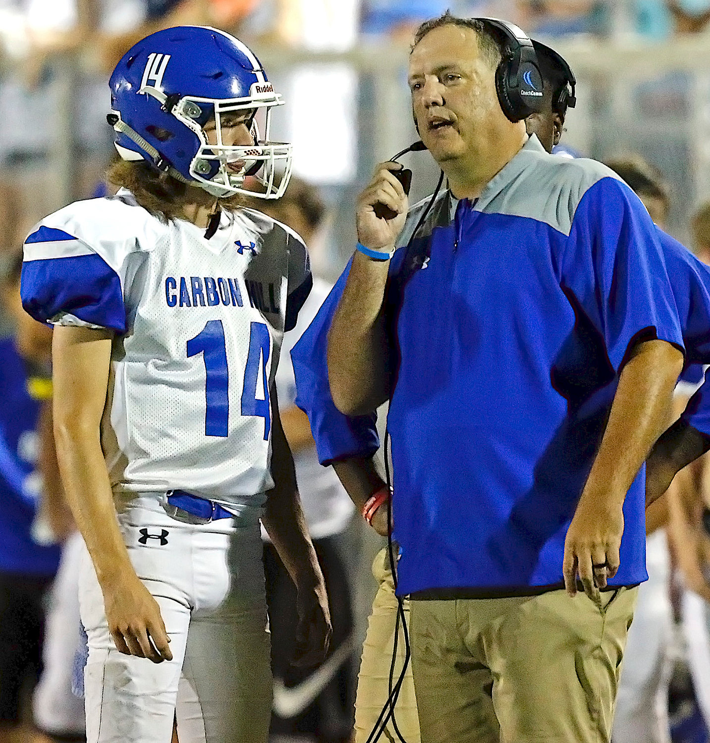 Carbon Hill football coach Scott Curd, right, talks with quarterback Jon Michael Madison during last season's game against Oakman. Curd is leaving his post after three years at the helm of the program. He led the Bulldogs to a 5-5 mark in 2018.