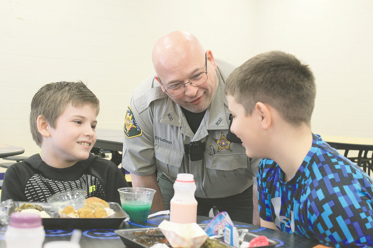 Brent Hudson, the new school resource officer in Curry, chats with students during their lunch period on Thursday.