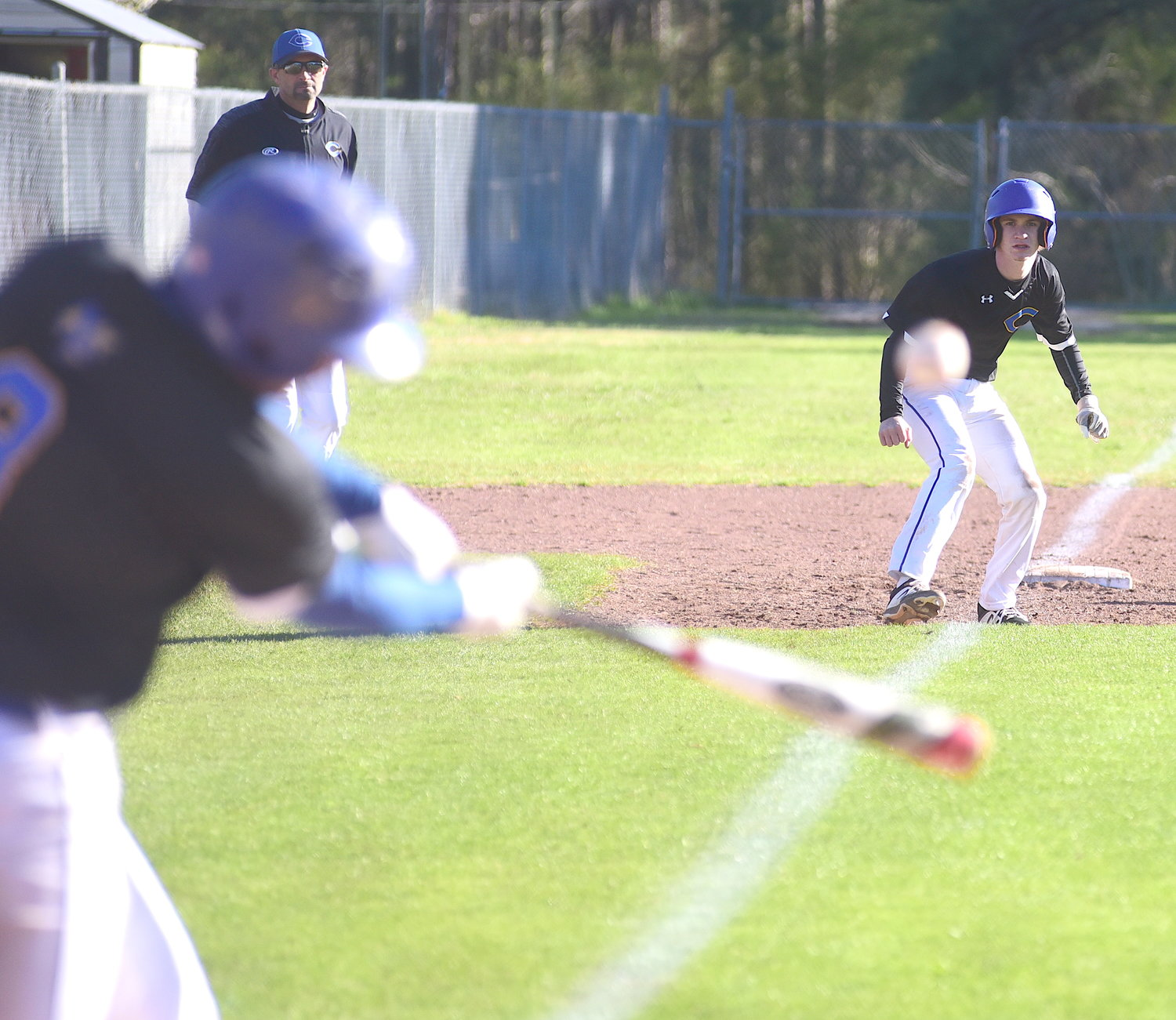 Curry's Luke Tidwell swings as Aaron Oswalt takes a lead off third base during Tuesday's Walker County Tournament game against Carbon Hill. Tidwell doubled on the play, scoring Oswalt. Curry won 3-2.
