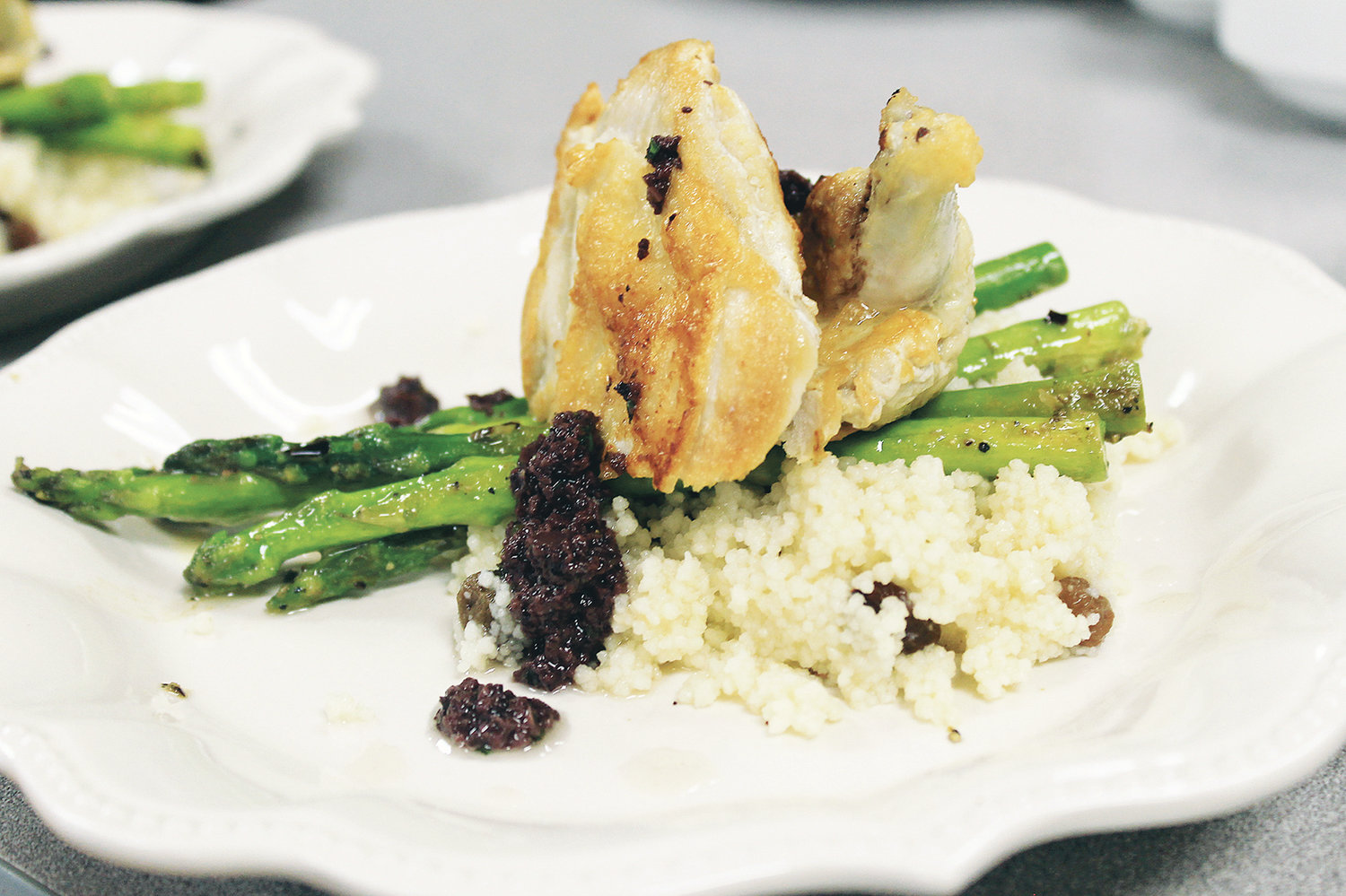 Chef Jonathan Fagan cooked chicken, couscous and asparagus during a cooking demonstration last month for representatives of area agencies that work closely with HarborChase of Jasper.