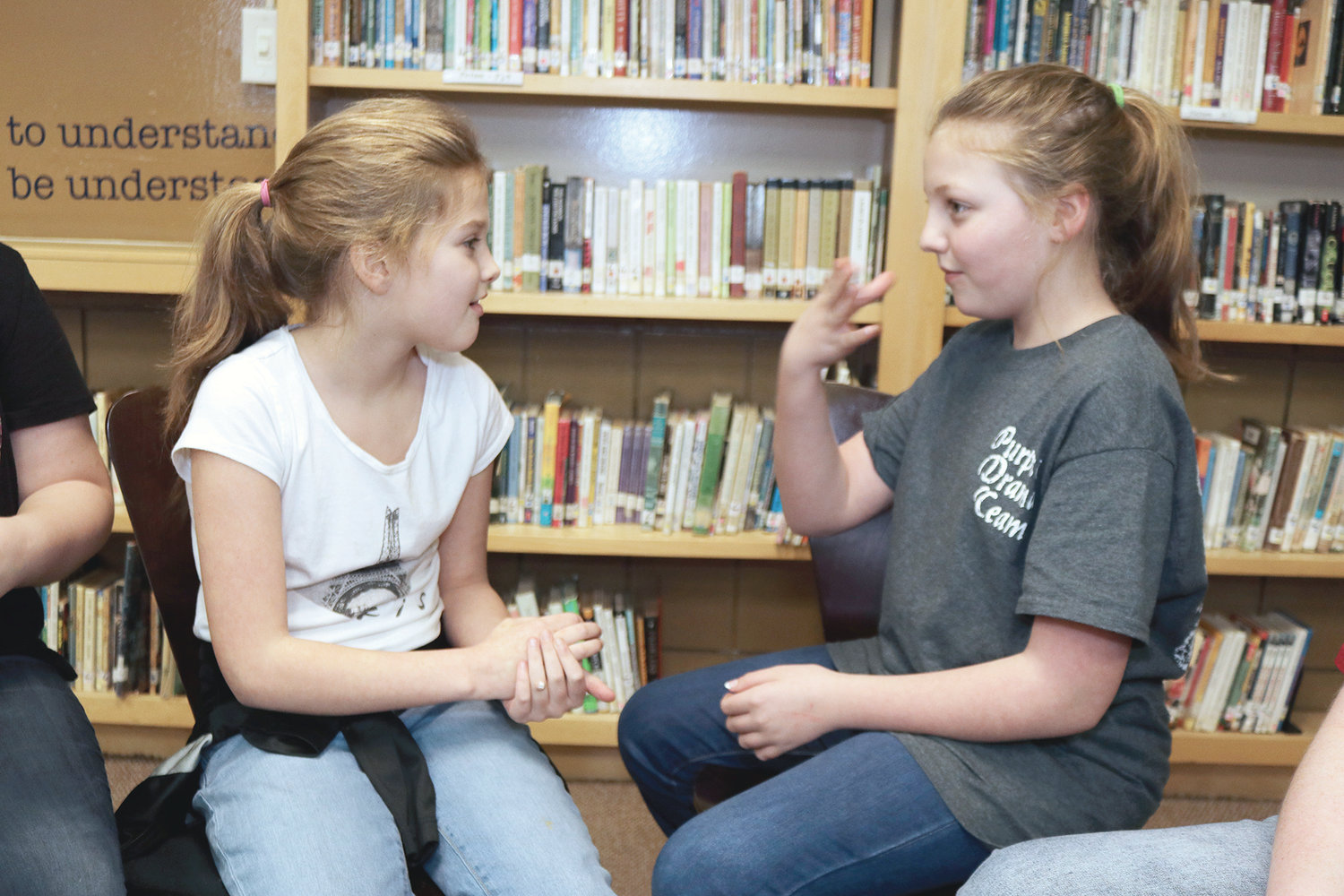 Sarah Wilkinson and Briley Adams communicate with sign language in the library at Sumiton Middle School. The two are members of the American Sign Language Club at the school.