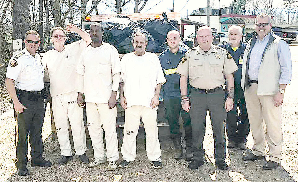 Sheriff Nick Smith, far left, and District Four Commissioner Steven Aderholt, far right, pose with inmates who picked up trash on Tuesday, March 12.