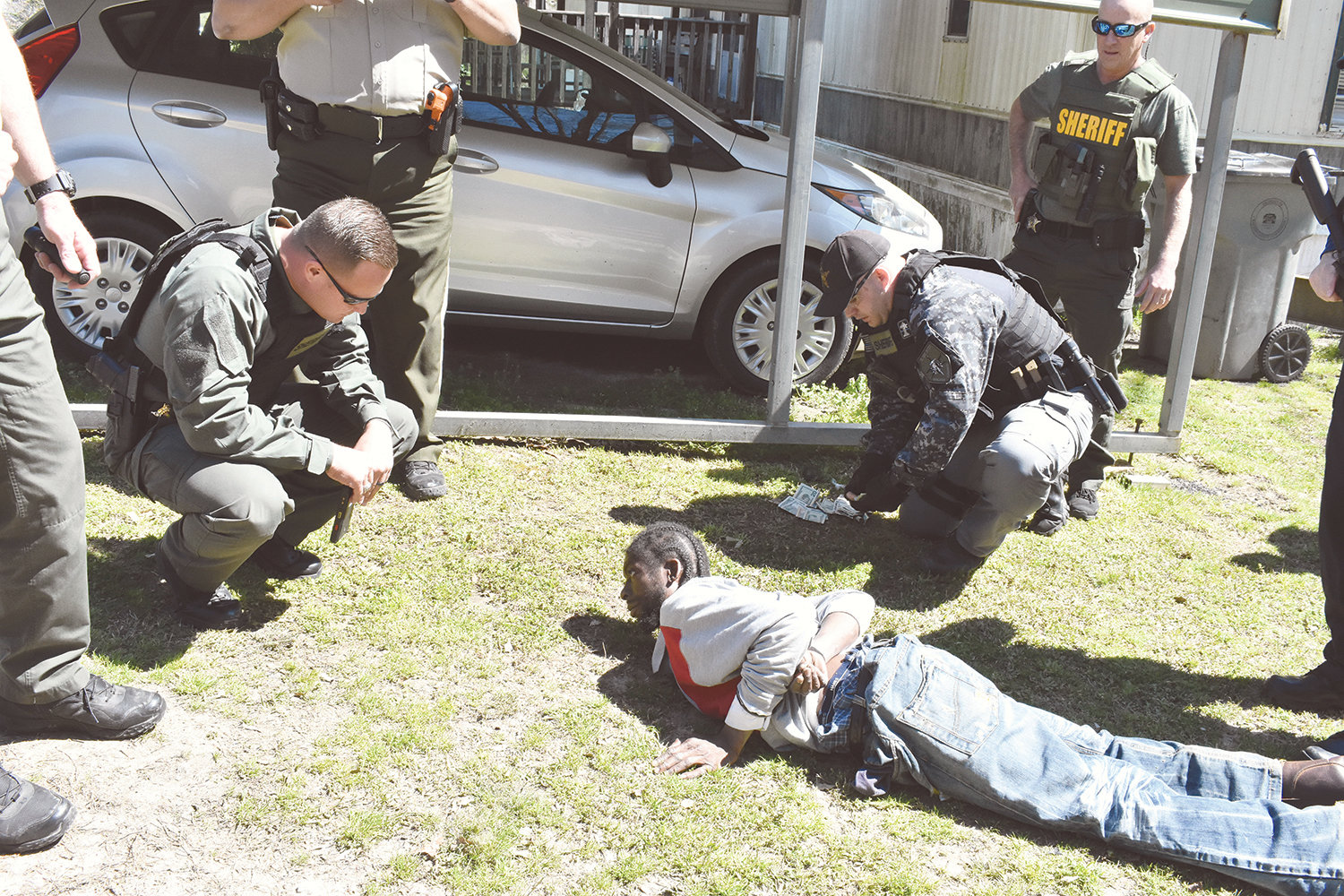 "Marvin Dewayne (""Skillet"") Patton, 40, of Sipsey, lies on the ground, while Walker County Nick Smith, kneeling, talks to him and another deputy in the background counts confiscated money. Patton was arrested in a Sipsey raid Friday for distributing heroin."