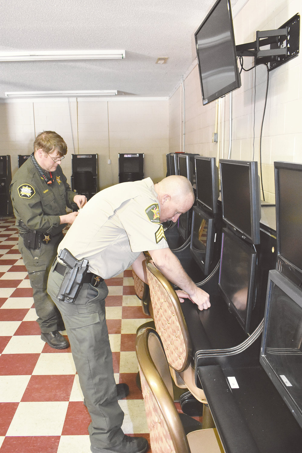 Walker County Sheriff deputies label 40 electronic bingo machines as evidence after they were confiscated in a raid Friday off Highway 5 on Brakefield Dairy Road.