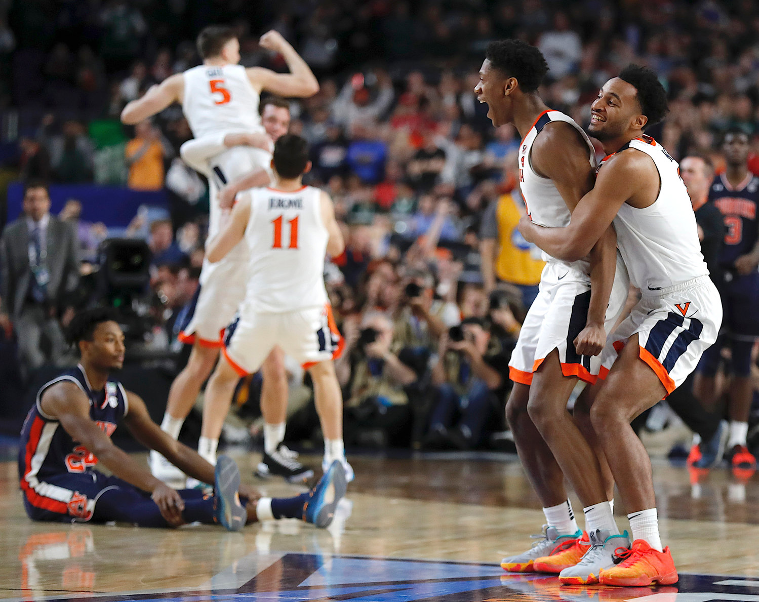 Virginia players celebrate at the end of a semifinal round game against Auburn in the Final Four NCAA college basketball tournament, Saturday, April 6, 2019, in Minneapolis.