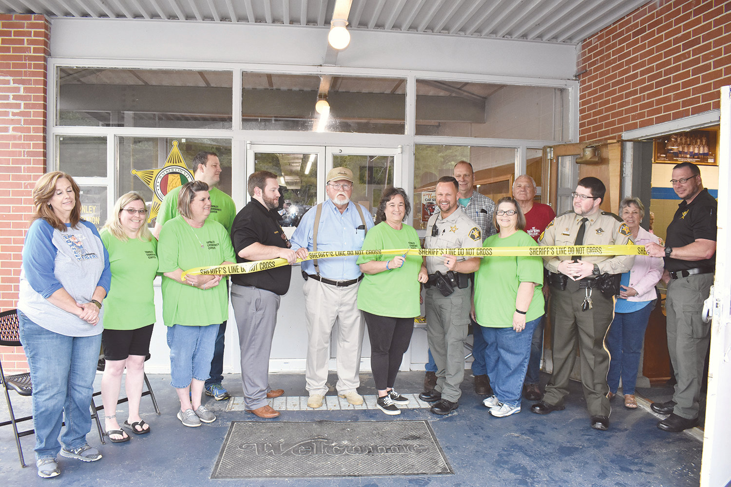 Denise Clements, the president of the Townley Community Center, cuts the ribbon to the new Walker County Sheriff's Substation at the center on Saturday, while Sheriff Nick Smith, Walker County Commission Chairman Jerry Bishop and others look on. State Rep. Tim Wadsworth, R-Arley, who is funding cameras for the substation, watched behind the camera.