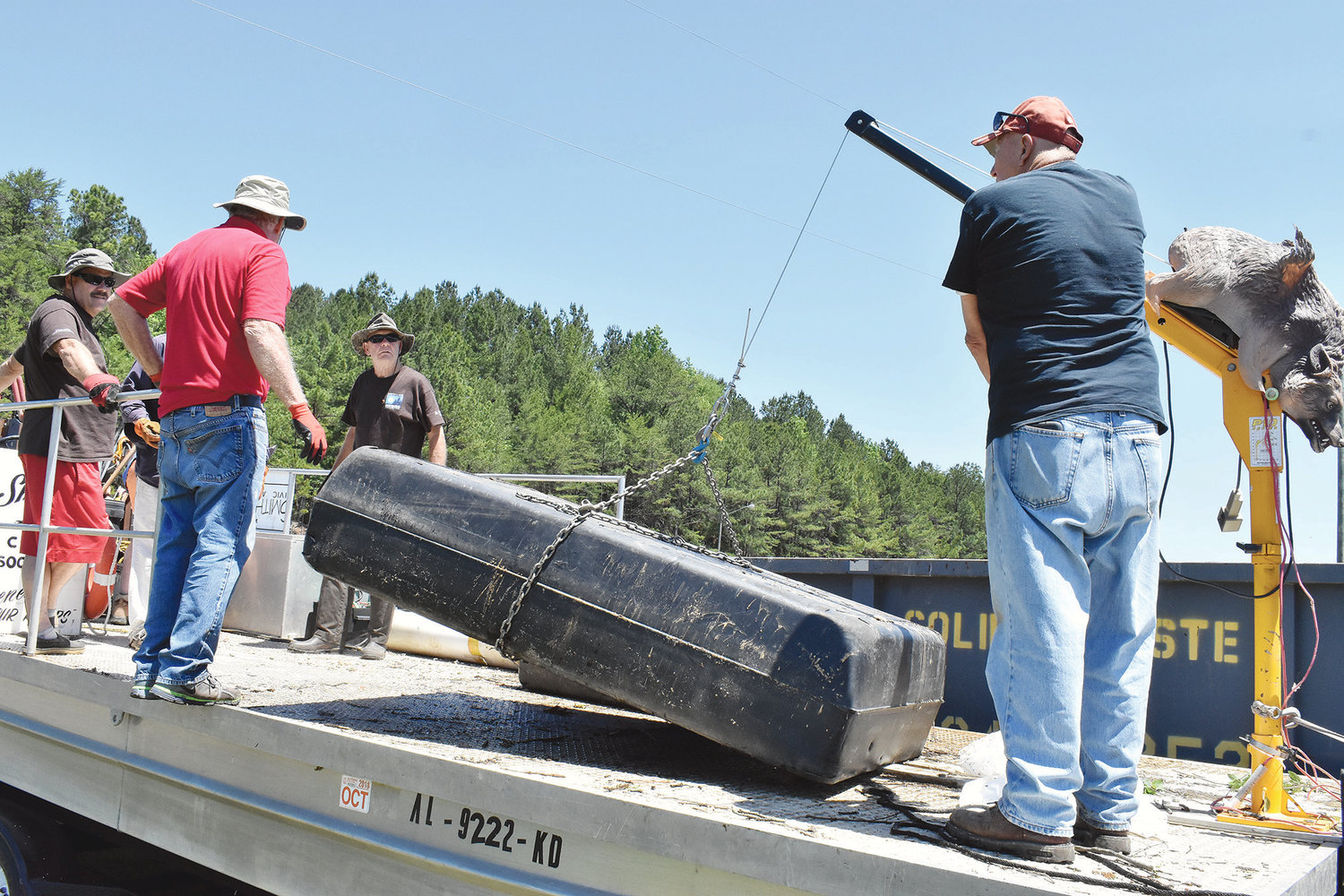 Volunteers hoist up heavier items into the Walker County Solid Waste Department dumpster in the wake of a spring cleanup at Smith Lake that started Monday and was to continue today.