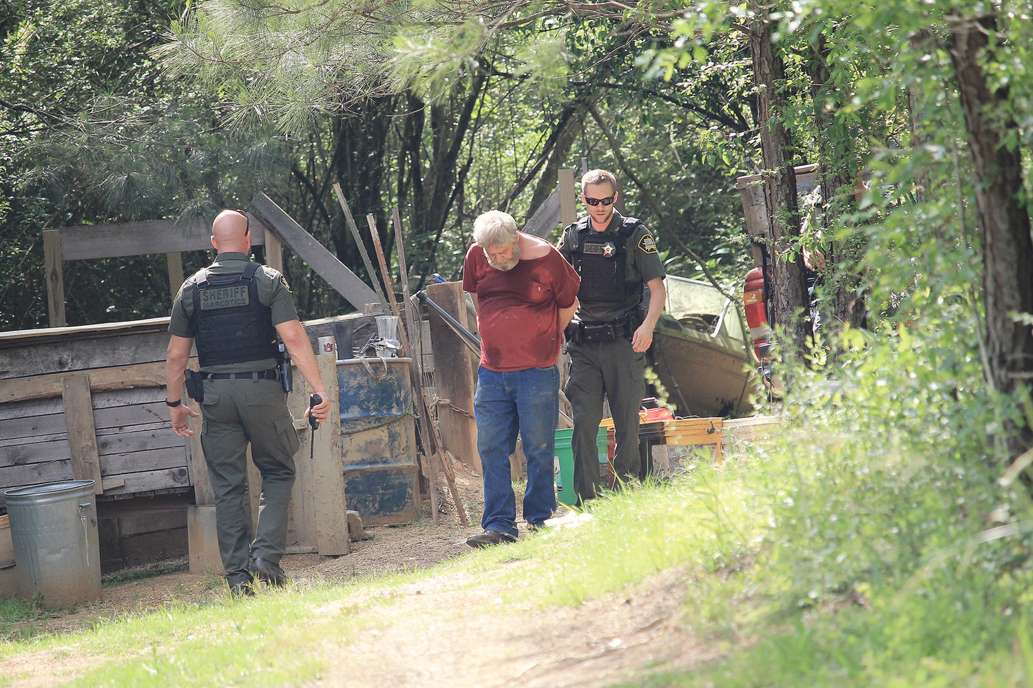 Slade Reeves walks Roger Dale Randolph out of the woods near his Oakman home during Wednesday's operation.
