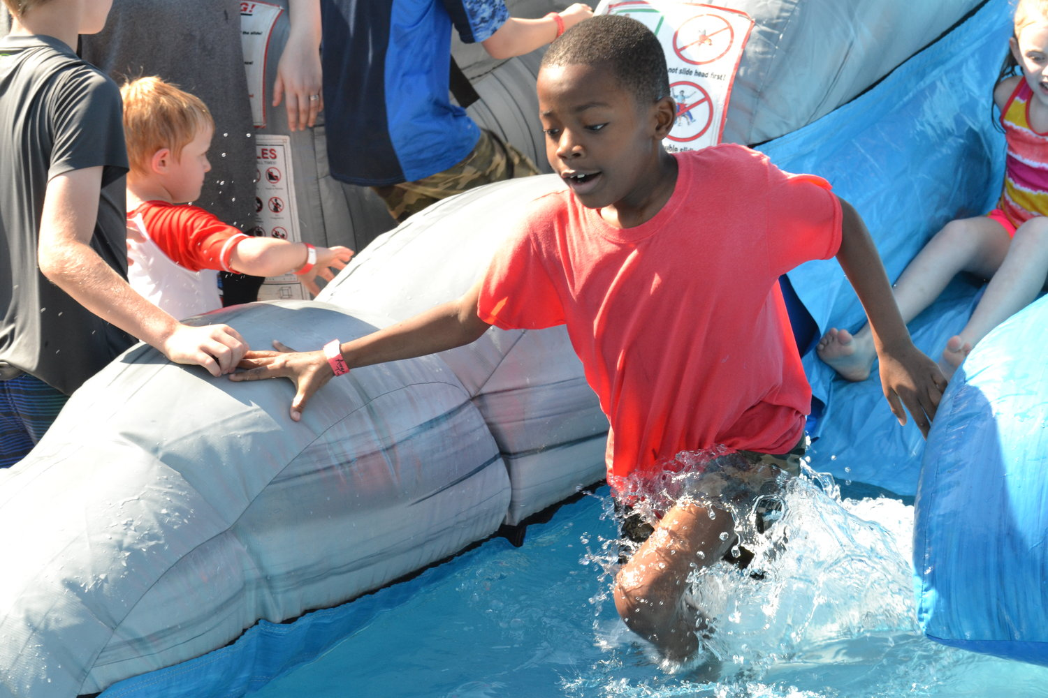 "Splashing down at the bottom of an inflatable water slide, students stayed cool at Cordova Elementary's annual ""May Day"""
