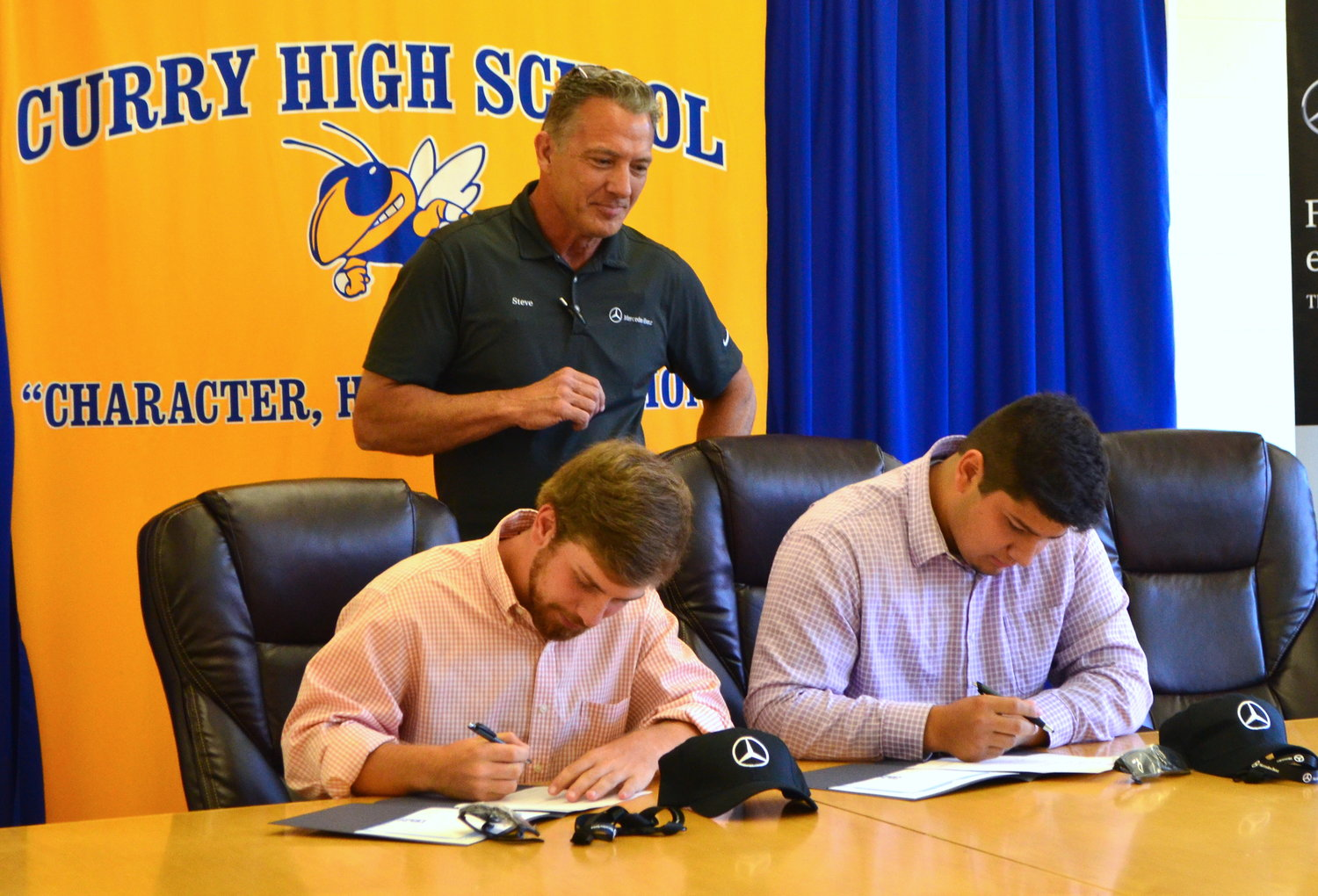 Curry seniors Tristan Jones and Martin Martinez have signed for a career opportunity with Mercedes-Benz. Overlooking is Mercedes-Benz Organizational Development Specialist Steve Colburn.