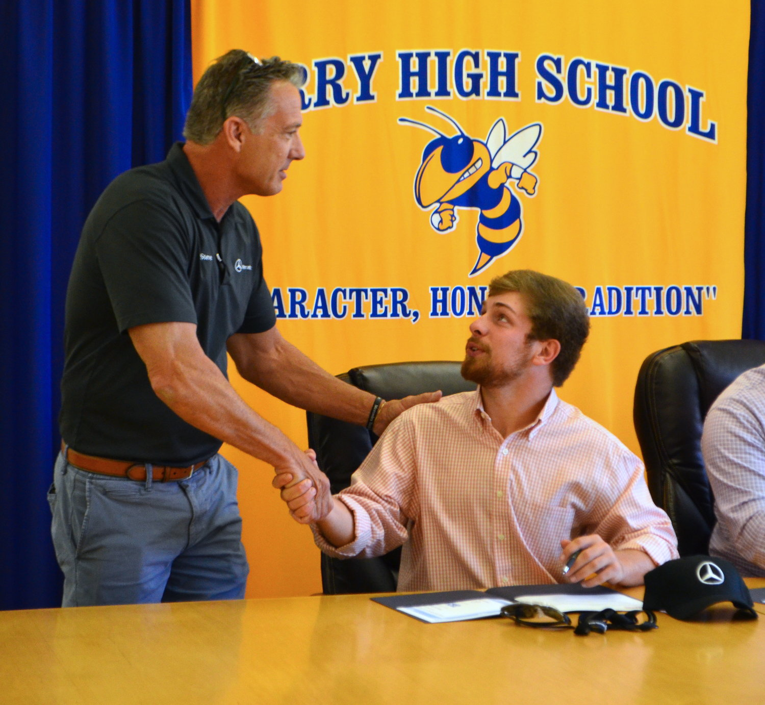 Curry senior Tristan Jones shakes hands with Steve Colburn of Mercedes-Benz after he signed for a career opportunity with Mercedes-Benz.