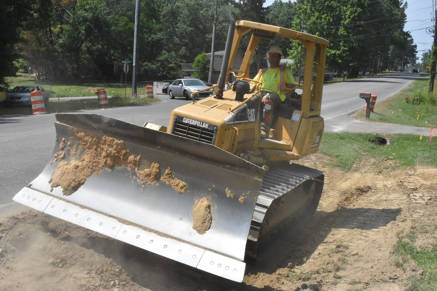 Crew member Adam Hudson of Jasper, who works for Carcel & G Construction, LLC of Hanceville, uses some heavy equipment on the Airport Road project Monday. A residential driveway  was cut through and replaced on Monday, as well as new pipe laid.