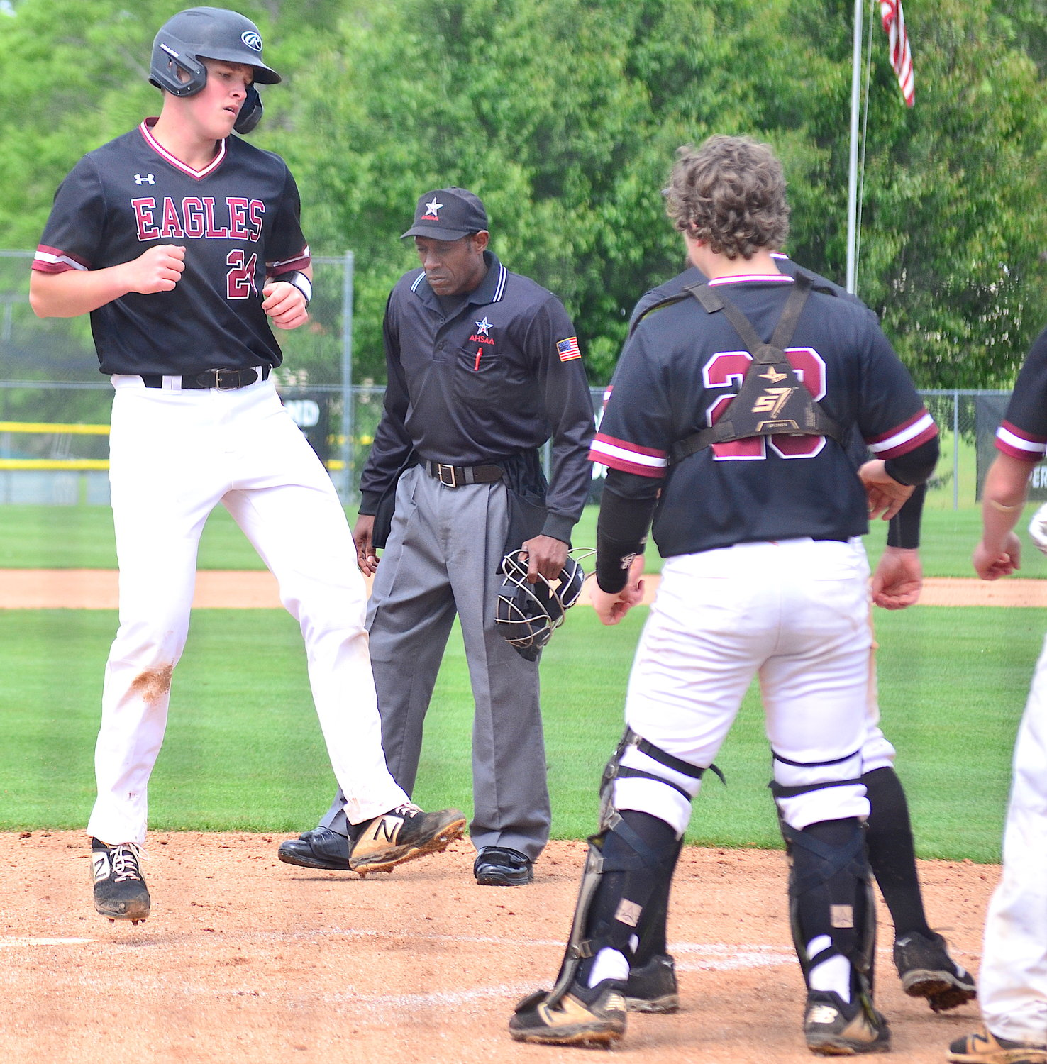 Sumiton Christian's Joe Hicks (24) is welcomed at home plate by teammates after belting a home run in the Eagles' first-round playoff series against Ohatchee.