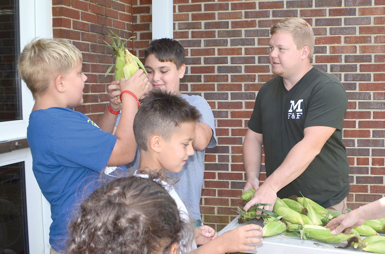 Farmer Drake McKenzie gives ears of corn to students prior to teaching them how to shuck the vegetable.