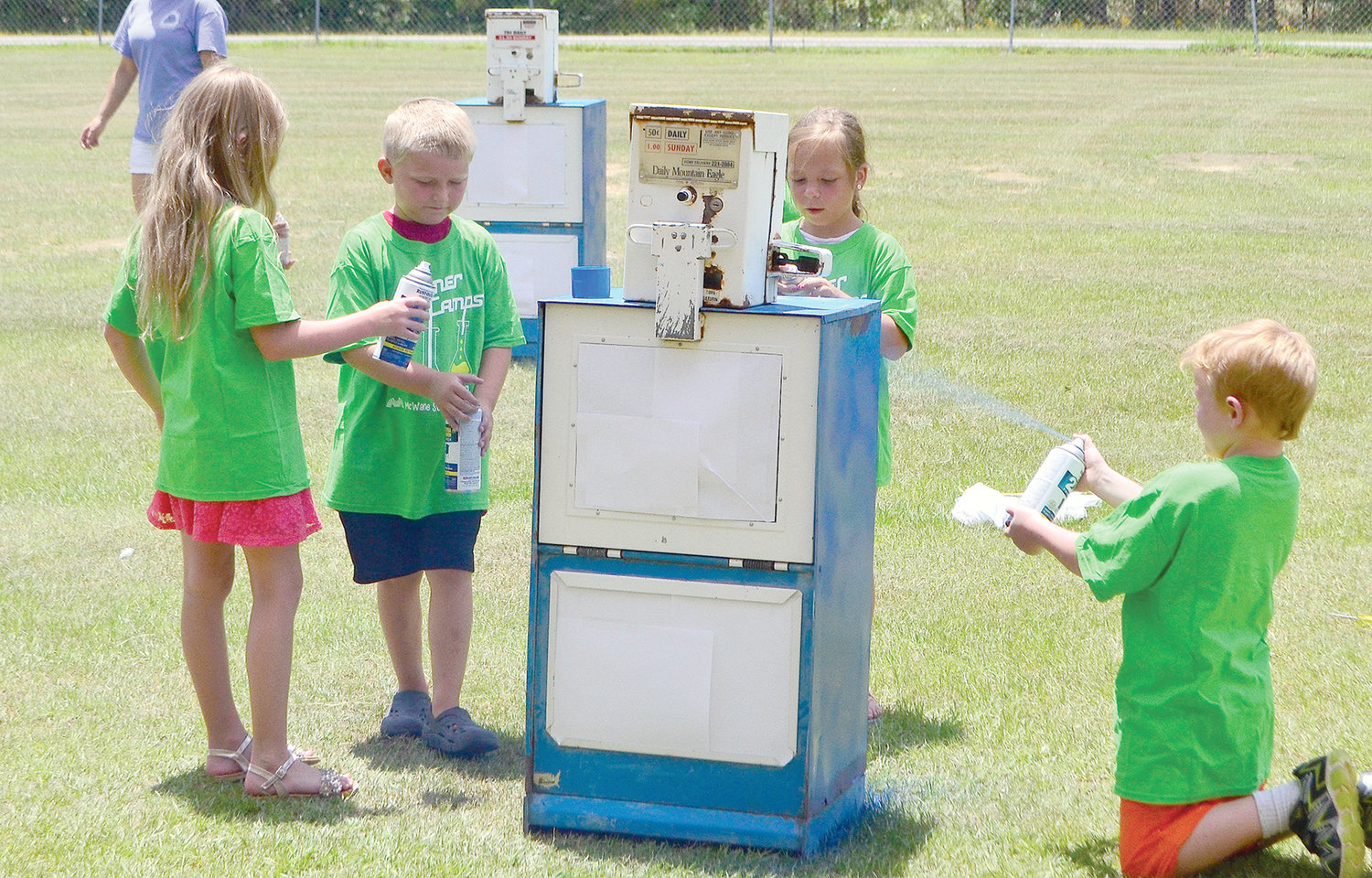 Students were busy spray painting old newspaper boxes on Tuesday. The boxes will be filled with books and placed throughout Carbon Hill to serve as little libraries.