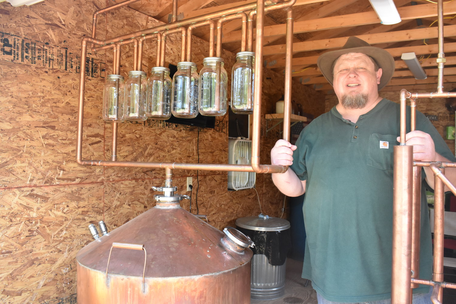 "Jimbo Bray of Carbon Hill shows off his still, with the jars used to blend in his special pineapple flavor, that will be featured in Tuesday's competition episode of ""Moonshiners"" on the Discovery Channel."