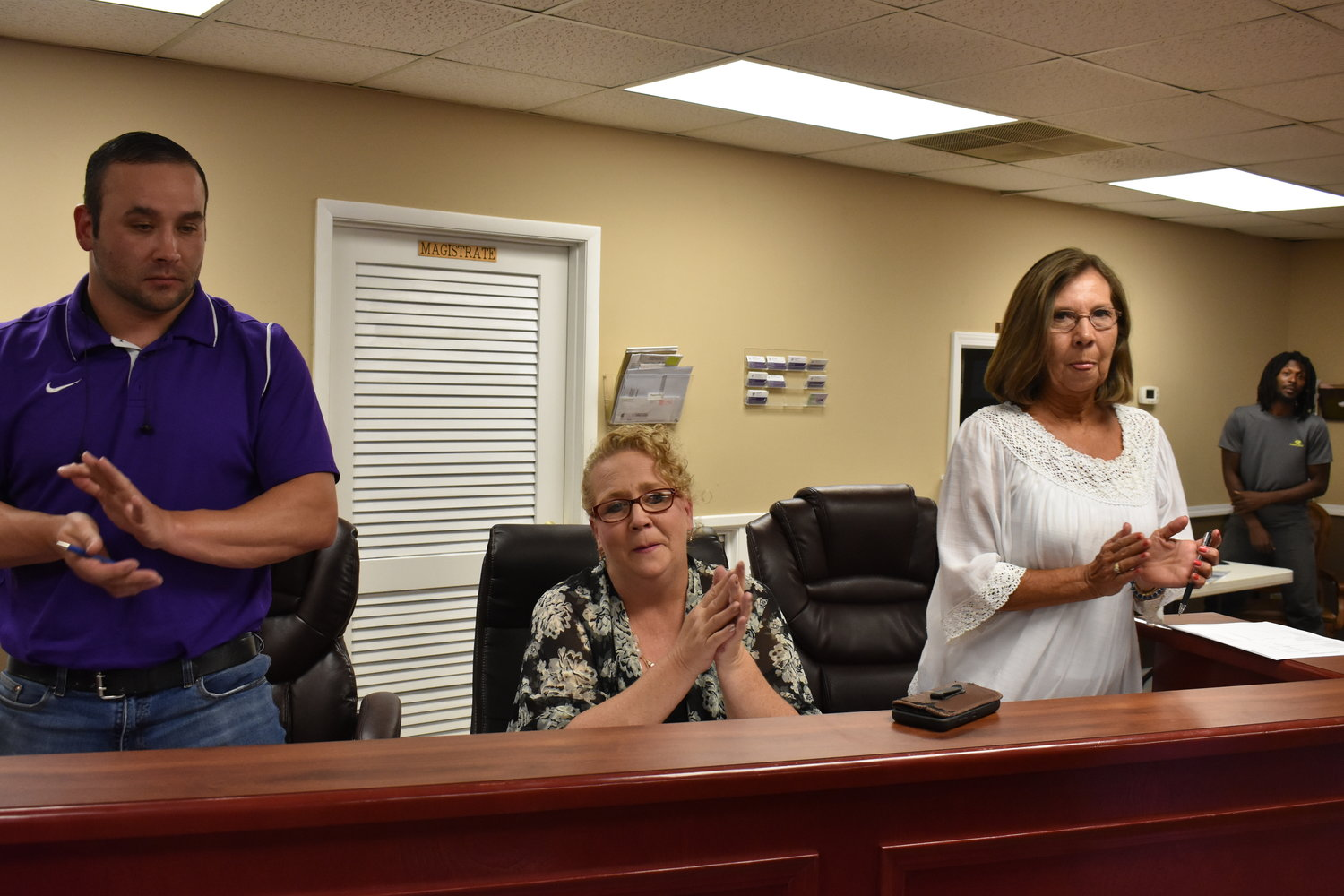 Parrish Mayor Heather Hall, seated, watches as she is given a spontaneous standing ovation during Tuesday night's Parrish City Council meeting, after she announced her resignation.