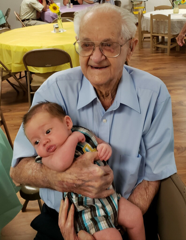 Bob Hester holds two-month-old Aiden Phillips. This photo documents the oldest and youngest member of Odom Memorial Baptist Church in Parrish.