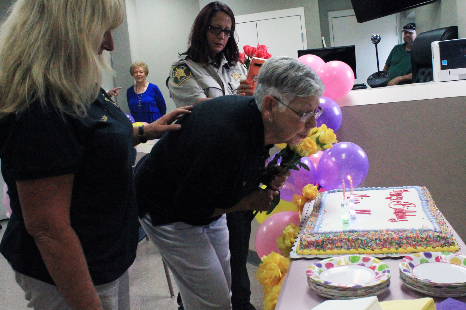 Longtime Walker County Sheriff's Office employee IV Rutledge blows out the candles on her cake during a surprise party on Wednesday.