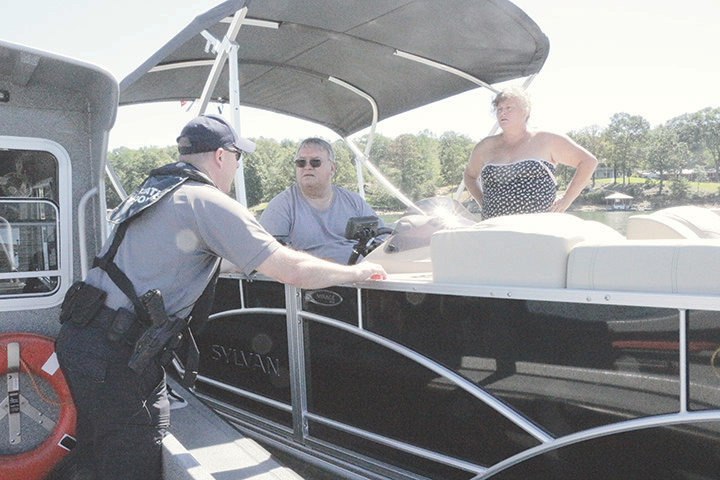 John Williams of the Marine Patrol Division of the Alabama Law Enforcement Agency chats with Tony and Gina Hunt of Brookhaven, Miss., who were enjoying a day on Smith Lake Friday morning.