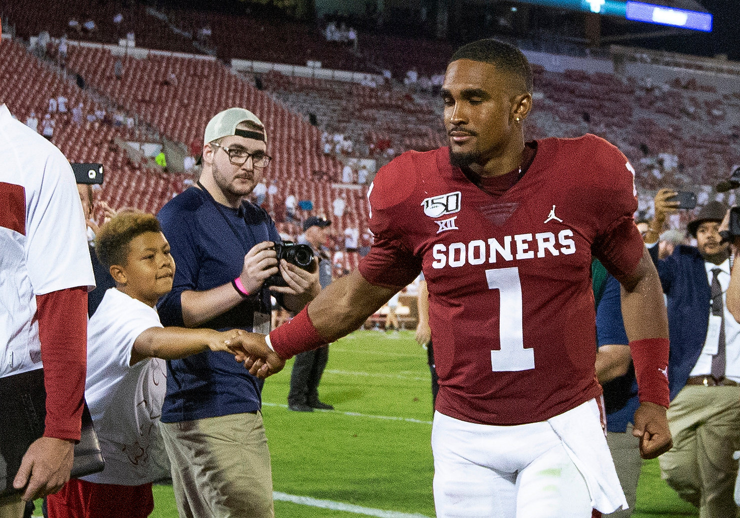 Oklahoma quarterback Jalen Hurts (1) greets a fan following the Sooners' 49-31 win  against Houston in Norman, Okla., Sunday, Sept. 1, 2019. (AP Photo/Alonzo Adams)