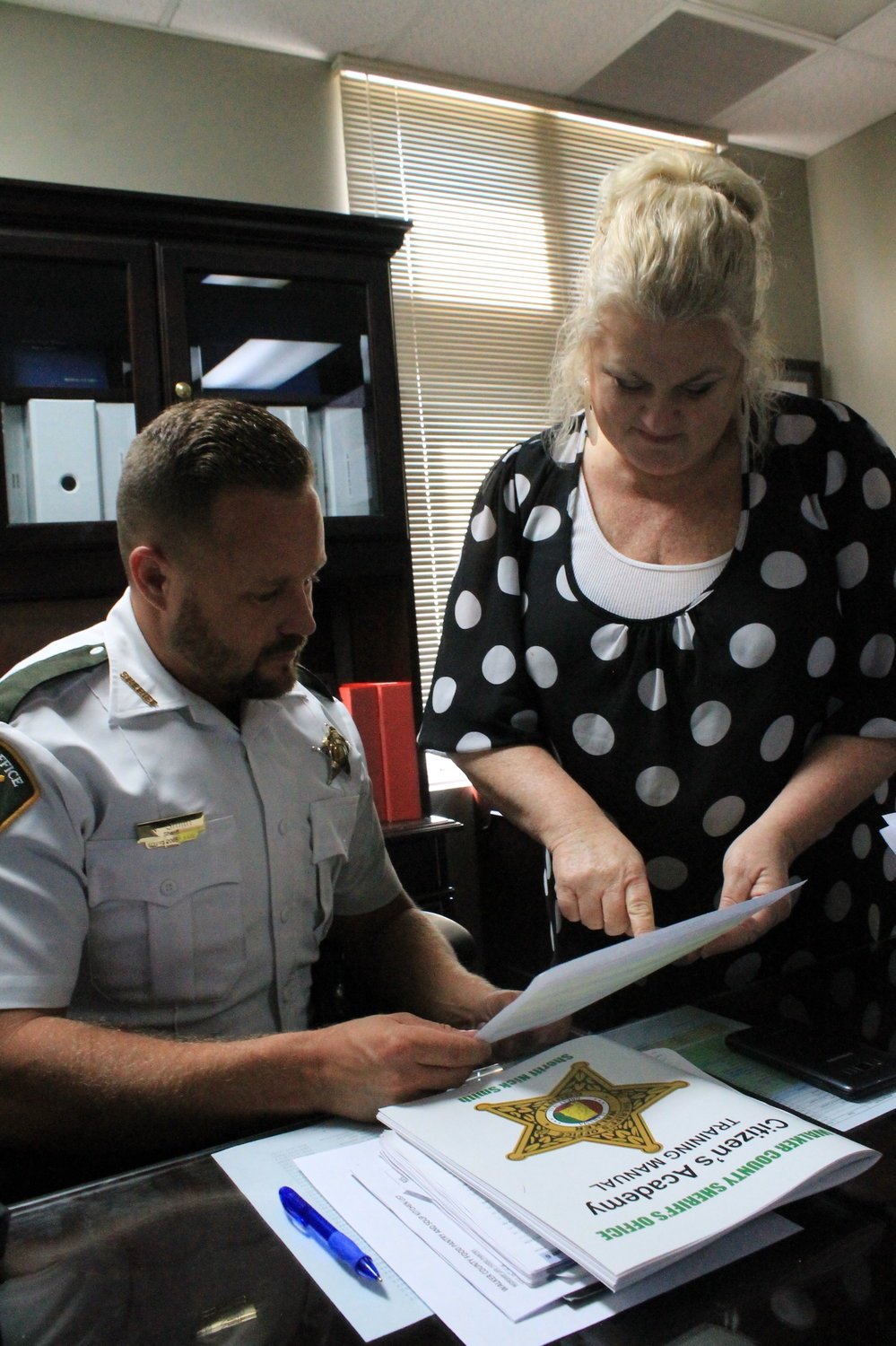 Administrative clerk Rhonda Guthrie goes over a calendar of commitments with Sheriff Nick Smith. Smith keeps a calendar for Smith, Chief Deputy Anthony Leach and Director of Operations Nick Key.