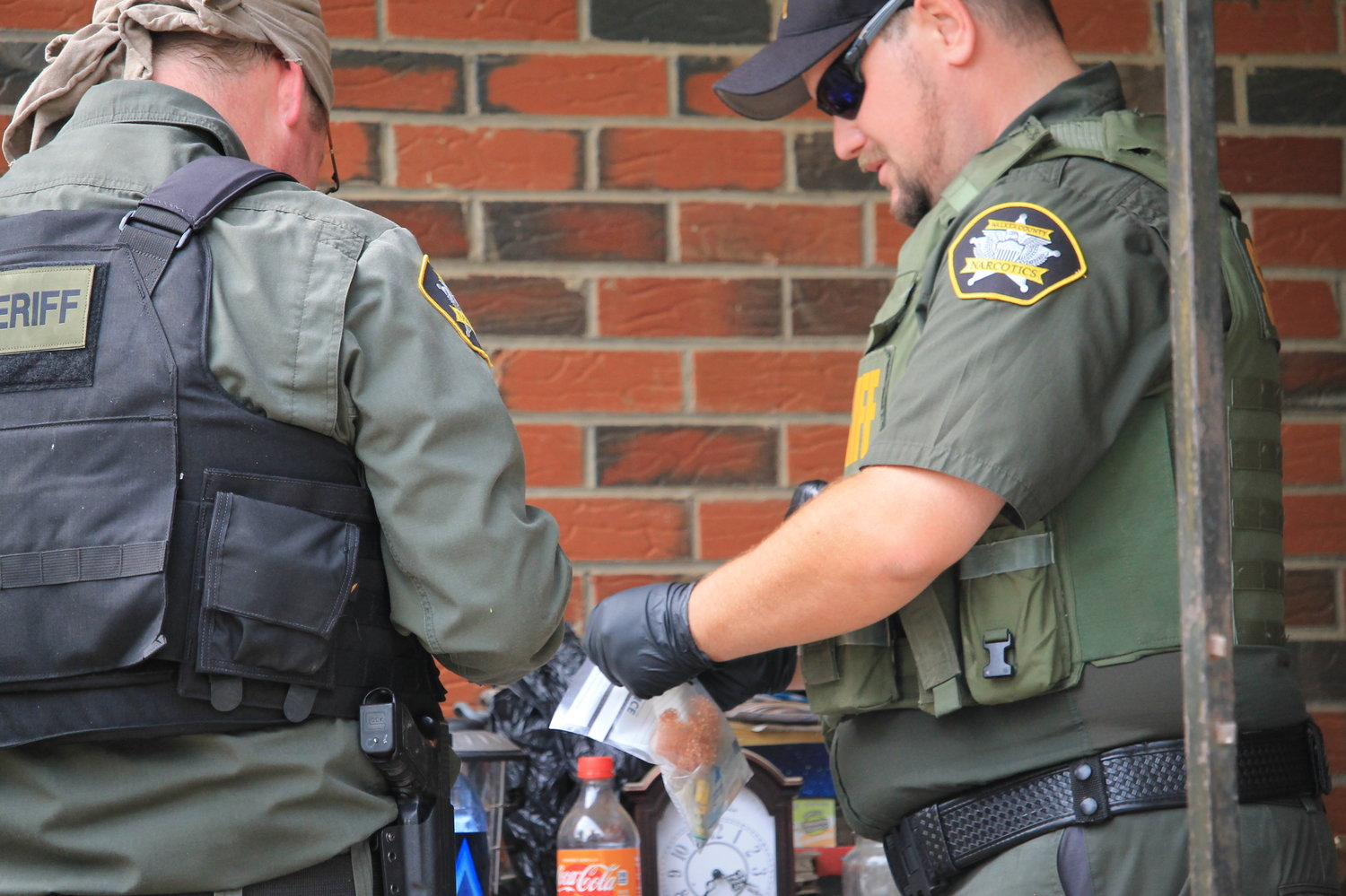 Members of the Walker County Sheriff's Office's narcotics unit collect evidence during a raid conducted in May.