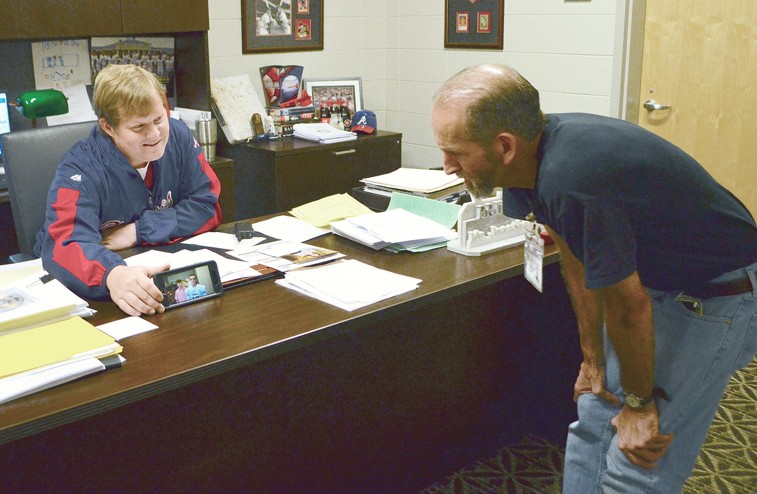Jasper High School Principal Jonathan Allen shows custodian Travis Kennedy a video of students talking about why they wanted to raise money to purchase the janitor a new truck.