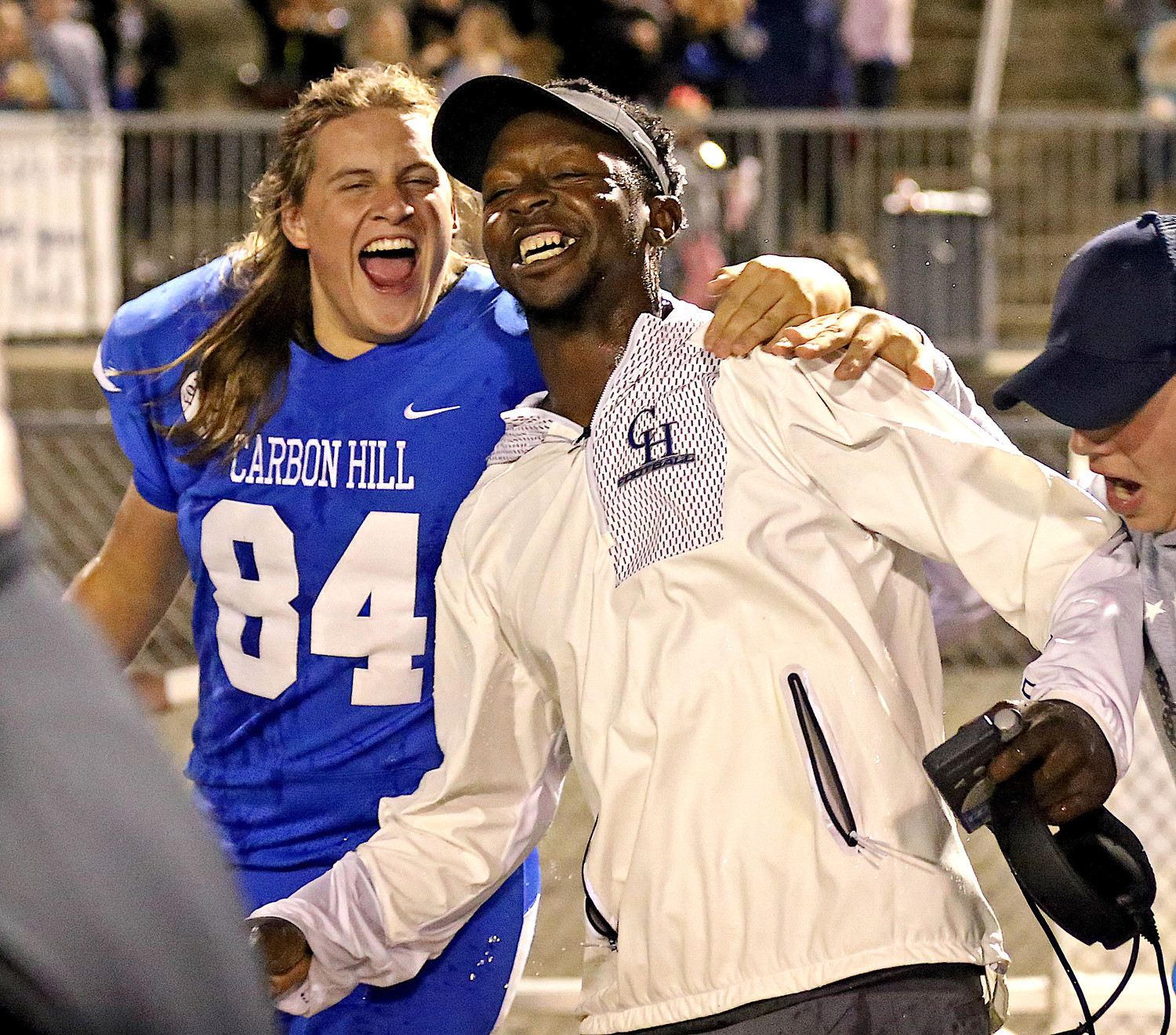 Carbon Hill coach Chavis Williams and senior Blake Garner celebrate the Bulldogs' 28-23 playoff-clinching win over Holt on Thursday night.