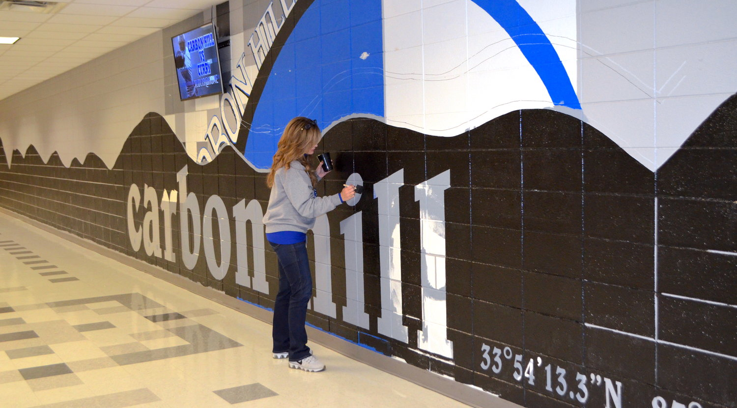 Carbon Hill High School librarian Tina McGee has spent the past week working on a large mural at the school. Once completed, the mural will resemble the Patagonia logo, with a Carbon Hill twist. As she painted after school on Friday, McGee explained the hills she has designed on the wall mirror a panoramic picture she took of hills behind the school's football field. The librarian has painted other murals around the school as well.