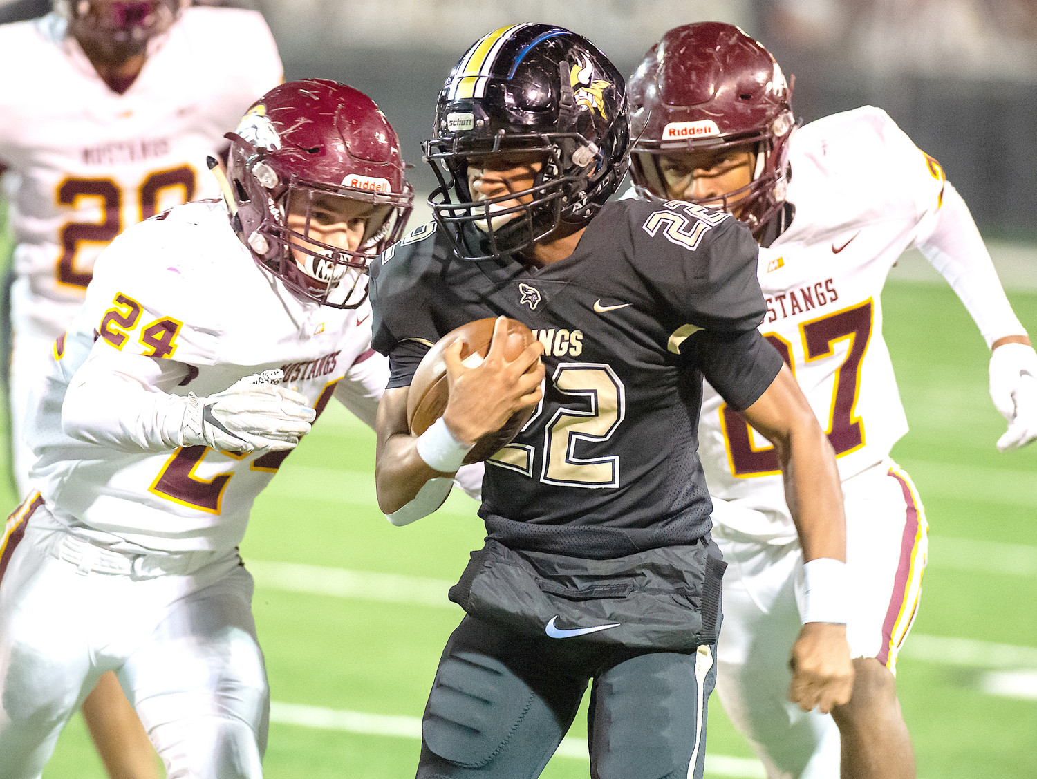 Jasper's Treyvon Stewart (22) runs between Madison Academy defenders Asa Barnett (24) and Jacobi McBride (27) during their Class 5A first-round playoff game at Ki-Ro Gambrell Field on Friday night. The Vikings won 55-14.