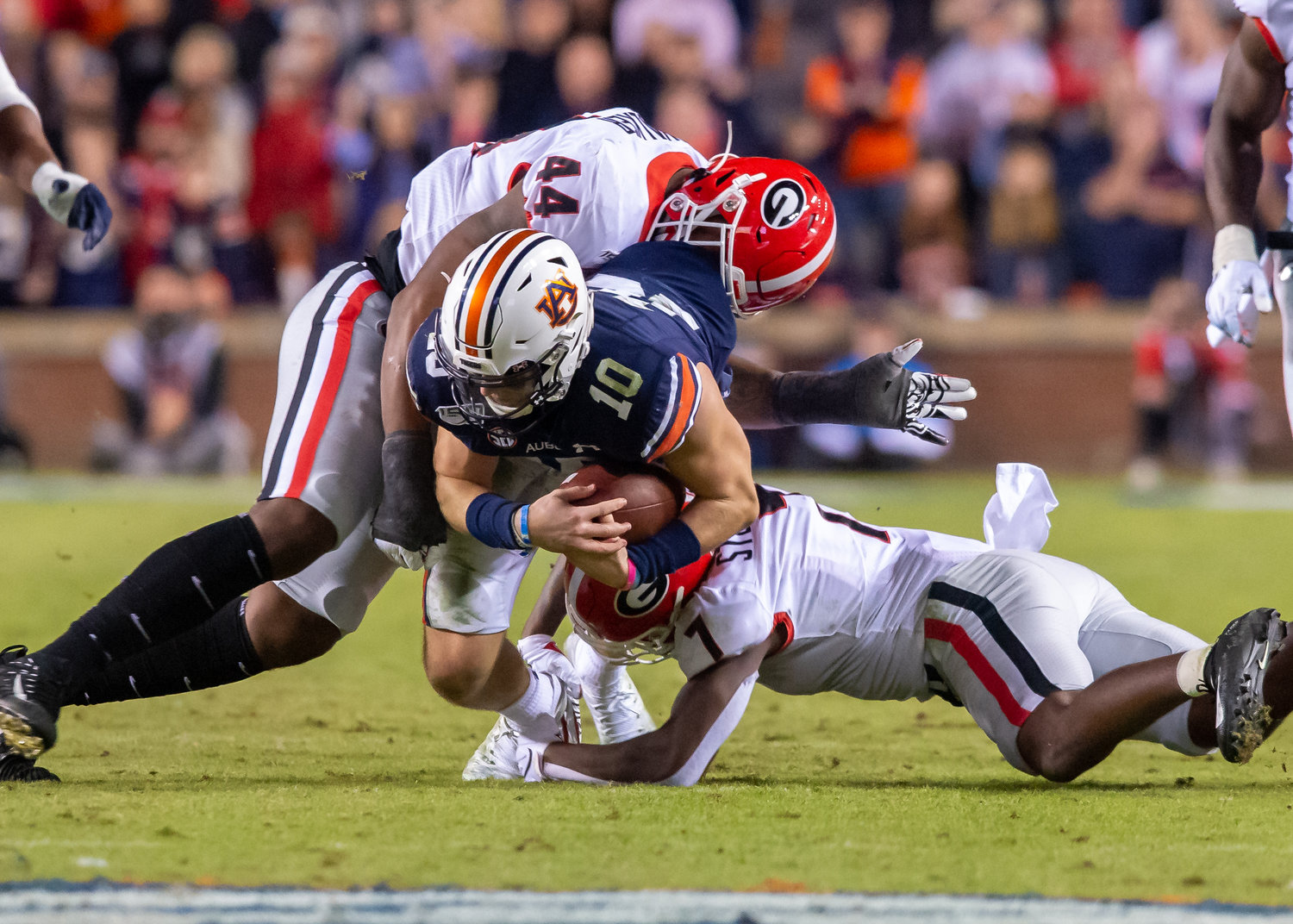 Auburn Tigers quarterback Bo Nix (10) is brought down by Georgia Bulldogs defensive lineman Travon Walker (44) and defensive back Tyrique Stevenson (7) during the second half of Saturday's game, at Jordan-Hare Stadium in Auburn,, AL. Daily Mountain Eagle -  Jeff Johnsey