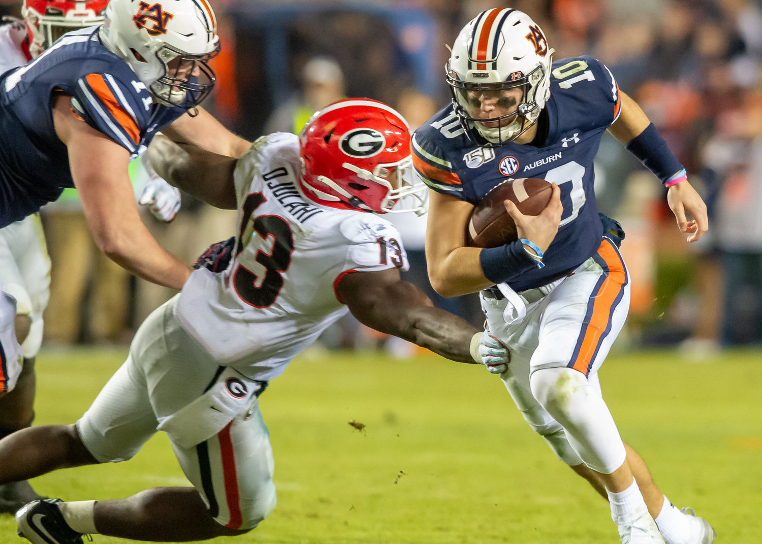 Auburn Tigers quarterback Bo Nix (10) runs past the outstretched arm of Georgia Bulldogs linebacker Azeez Ojulari (13) during the second half of Saturday's game, at Jordan-Hare Stadium in Auburn,, AL. Daily Mountain Eagle -  Jeff Johnsey