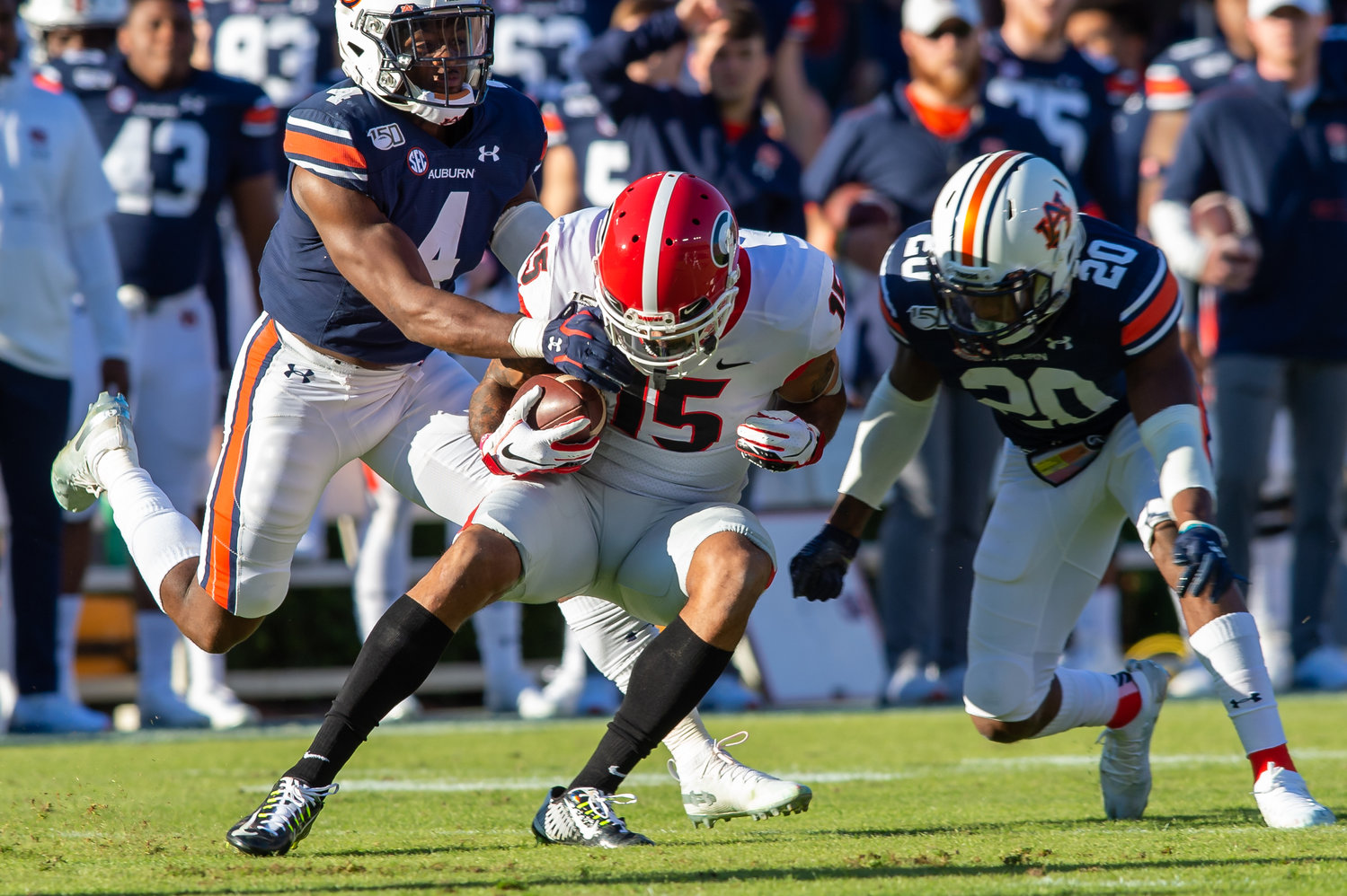 Auburn Tigers defensive backs Noah Igbinoghene (4) and  Jeremiah Dinson (20) tackle Georgia Bulldogs wide receiver Lawrence Cager (15) during the first half of Saturday's game, at Jordan-Hare Stadium in Auburn,, AL. Daily Mountain Eagle -  Jeff Johnsey