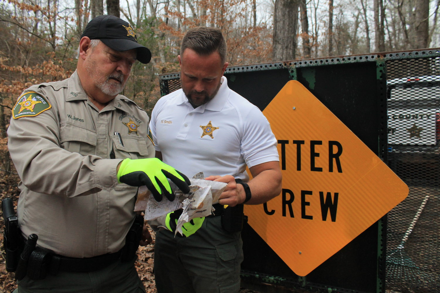 Wayne Jones, a corrections officer who supervises inmates working on one of the county's litter crews, shows Sheriff Nick Smith several documents that identify individuals believes to be responsible for illegal dumping.