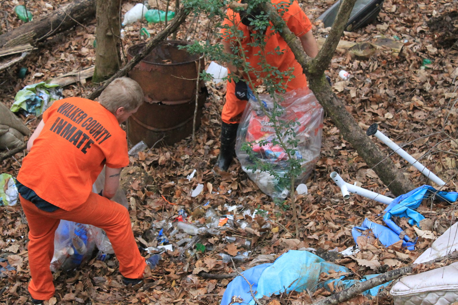 Two inmates pick up trash in east Walker on Friday.