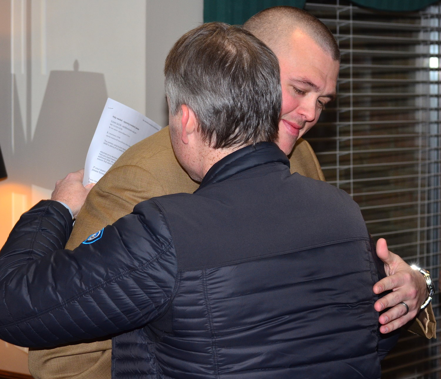 Philip Bailey hugs Jasper Board of Education member Scott Thornley after Wednesday's board meeting announcing Bailey as the Jasper head football coach.