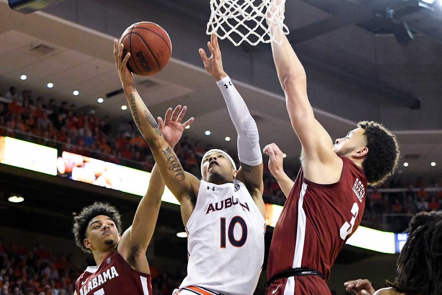 Alabama guard Jaden Shackelford (5) and Alabama forward Alex Reese (3) defend a shot by Auburn guard Samir Doughty (10) during overtime of Wednesday's game.