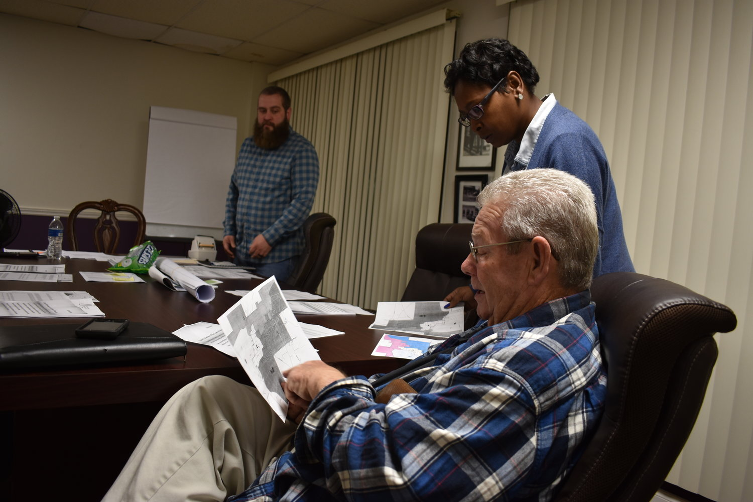 Parrish Town Councilman William Smith looks at district maps for the upcoming municipal elections before Tuesday night's council workshop. Mayor La'Tisha Oliver and Councilman Jake Williams look on.