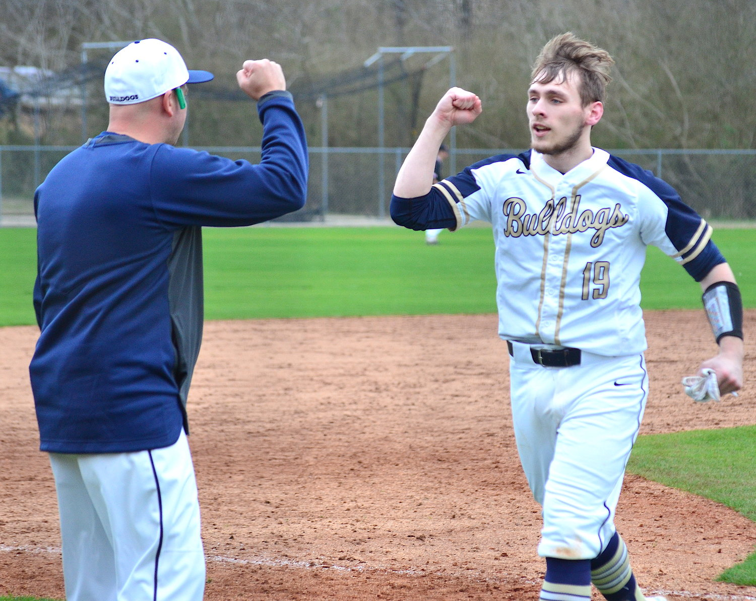 Dora's Zac Headrick (19) is congratulated by assistant coach Jeremy Willingham after Headrick doubled against Sumiton Christian on Monday. The Bulldogs opened the season with a pair of wins over the Eagles at Sumiton Christian's Blair Field, winning 9-4 and 13-5.