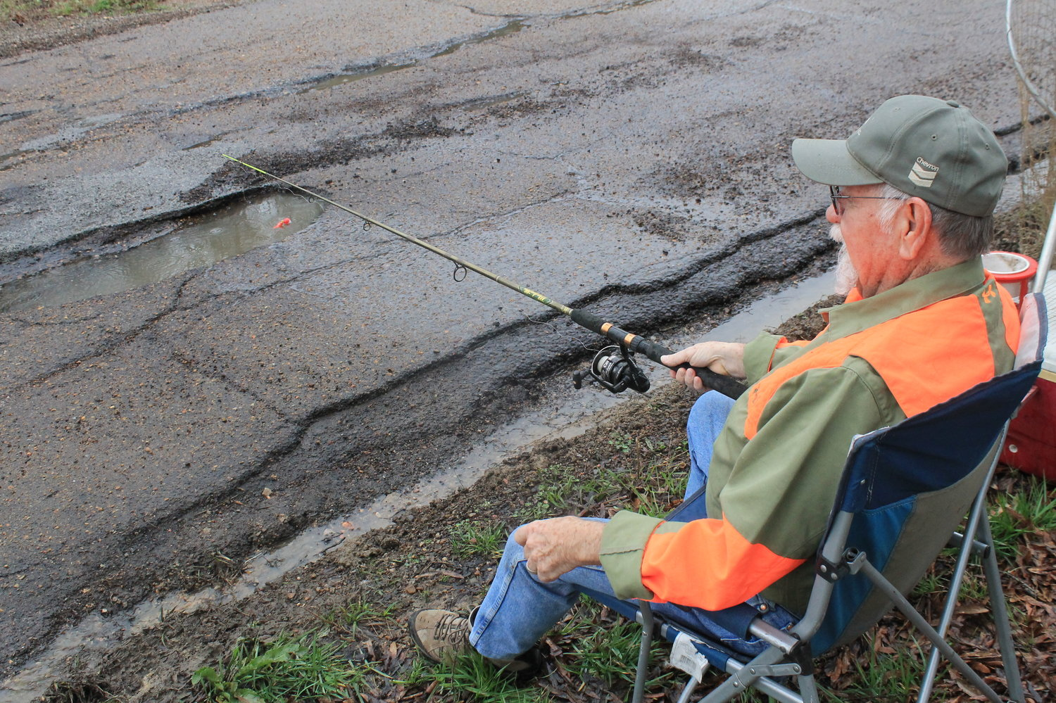 Cordova City Councilman Larry Sides pretends to fish in a pothole on Gardner's Gin Road recently during a rainy period to make a point about the potholes that dot the road.