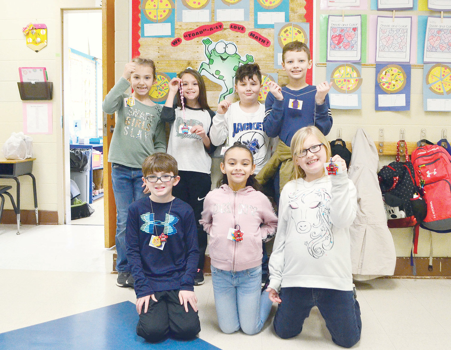 A group of students at Curry Elementary School shows off brag tags they have earned for good behavior, academics and more.