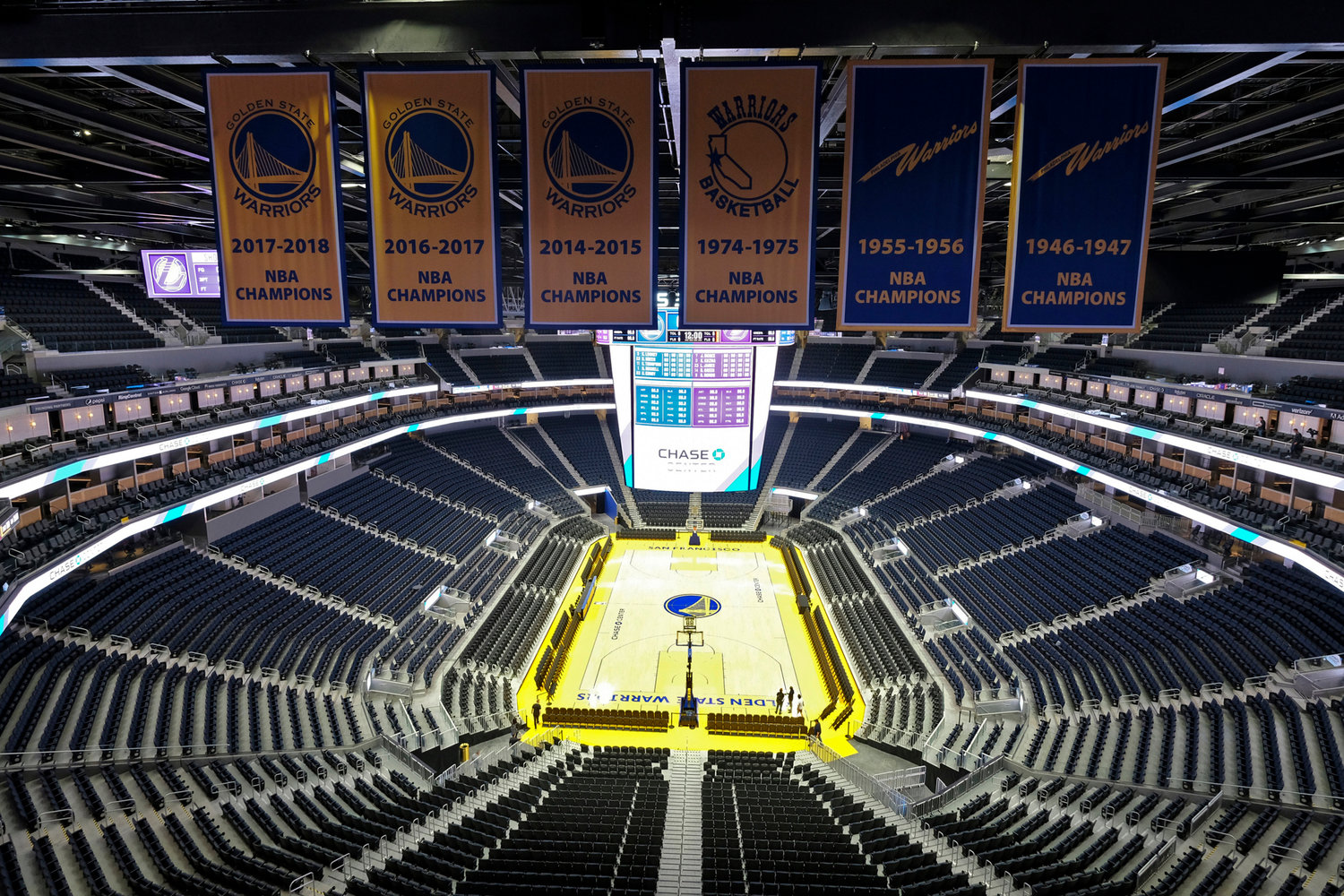 FILE - In this Aug. 26, 2019, file photo, the Golden State Warriors championship banners hang above the seating and basketball court at the Chase Center in San Francisco. The NBA became the first major American sports league to suspend play because of the coronavirus pandemic on Wednesday.