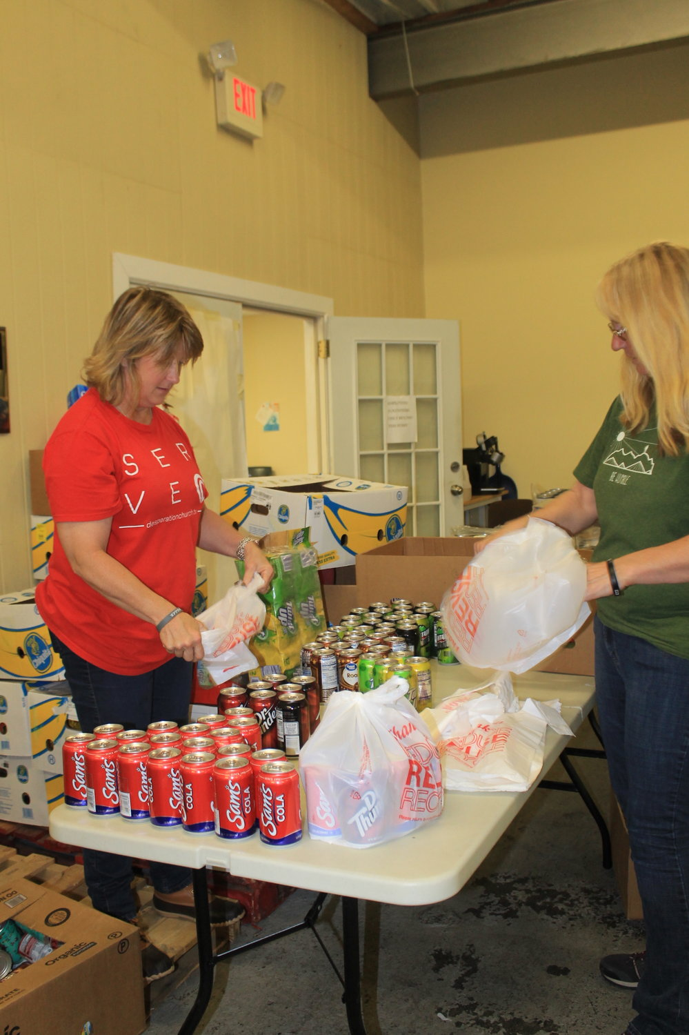 Volunteers pack bags of groceries at t on Monday afternoon.