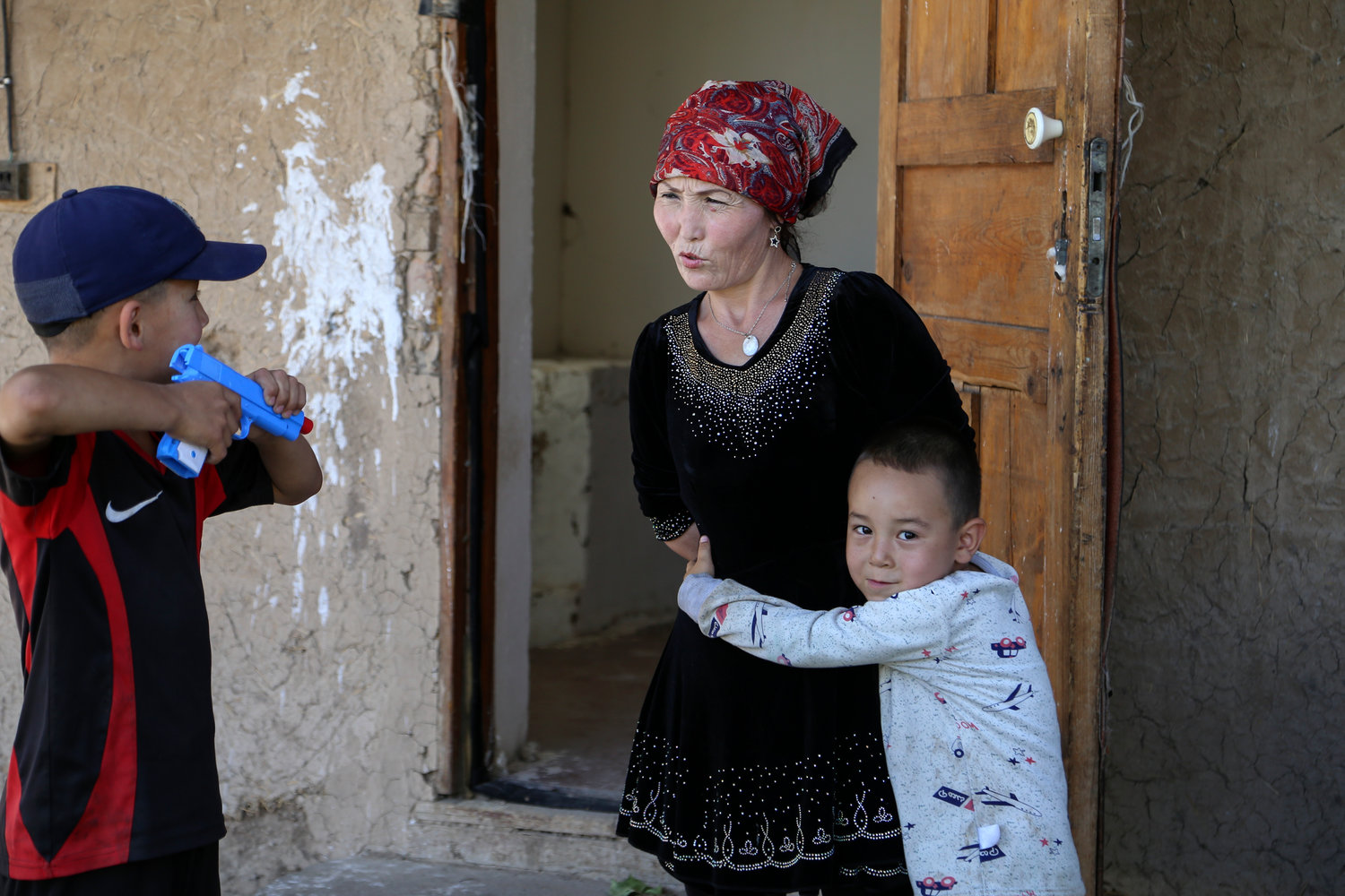 Gulnar Omirzakh plays with her son, Alif Baqytali, at their home in Shonzhy, Kazakhstan. Omirzakh, a Chinese-born ethnic Kazakh, says she was forcibly fitted with an intrauterine contraceptive device, and that authorities threatened to detain her if she didn't pay a large fine for giving birth to Alif, her third child. (AP Photo/Mukhit Toktassyn)