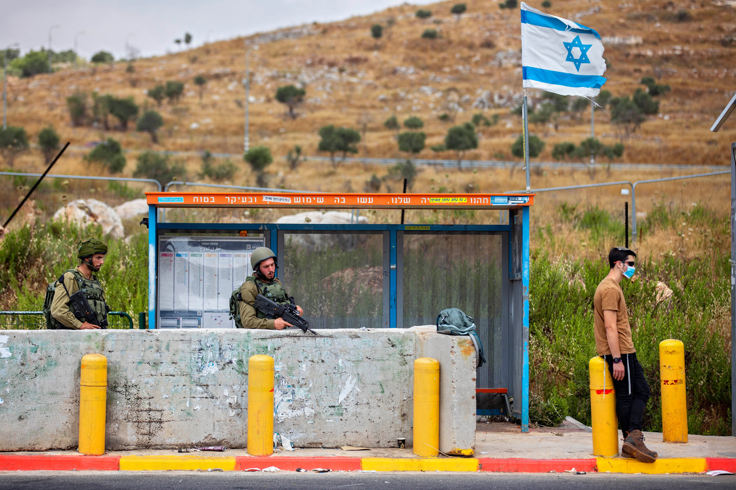 Israeli soldiers guard a bus station at the Tapuach junction next to the West Bank city of Nablus, Tuesday, June 30, 2020. Israeli Prime Minister Benjamin Netanyahu appears determined to carry out his pledge to begin annexing parts of the occupied West Bank, possibly as soon as Wednesday. (AP Photo/Oded Balilty)