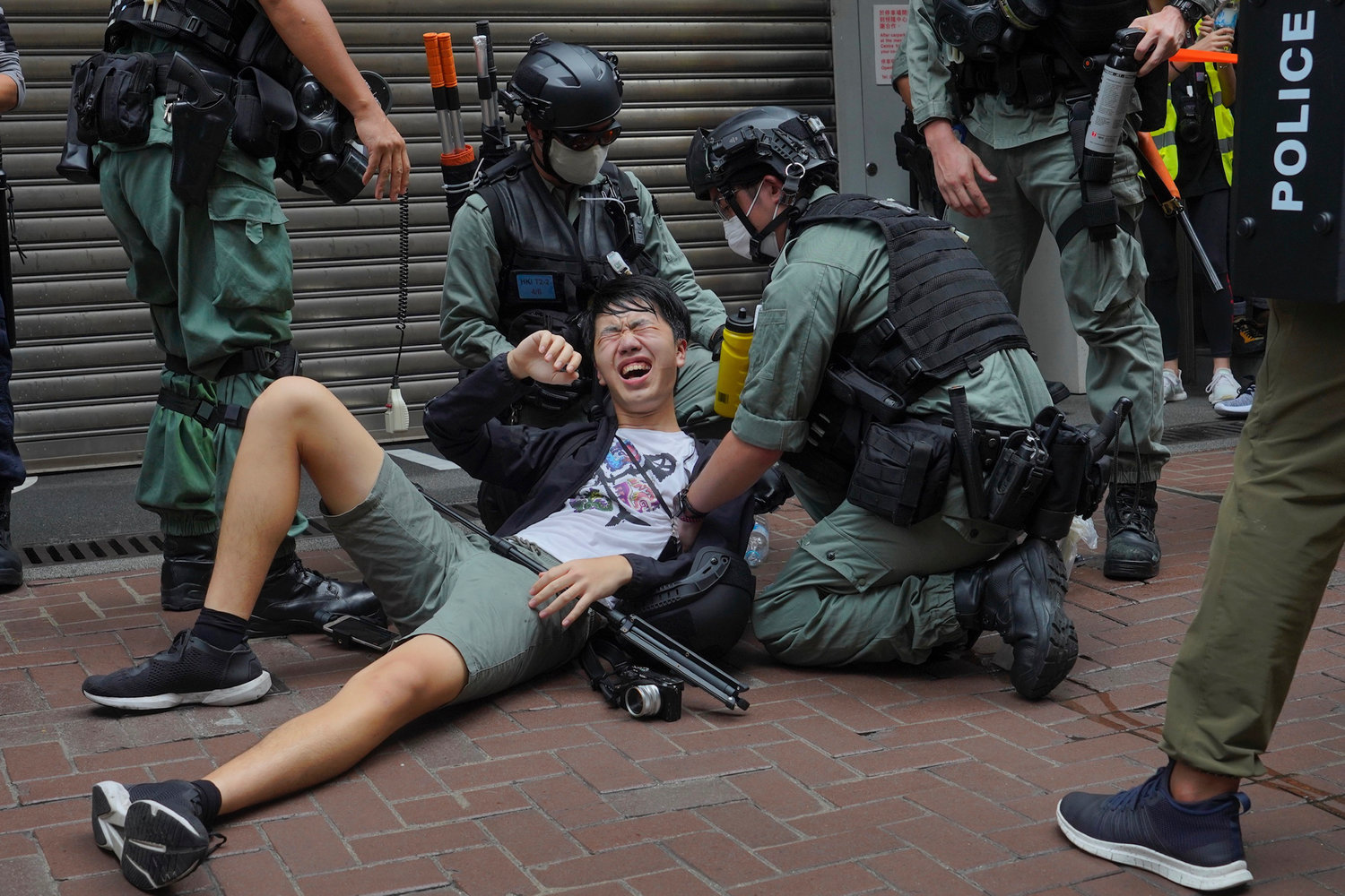 A reporter falls down after being sprayed with pepper spray by police during a protest in Causeway Bay during the annual handover march in Hong Kong, Wednesday, July. 1, 2020. Hong Kong marked the 23rd anniversary of its handover to China in 1997, and just one day after China enacted a national security law that cracks down on protests in the territory. (AP Photo/Vincent Yu)