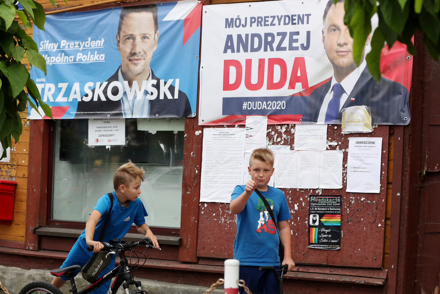 In this Thursday, July 9, 2020 photo election campaign posters of incumbent conservative president, Andrzej Duda, right, and his challenger, the liberal Warsaw mayor Rafal Trzaskowski, for a tight presidential election runoff on Sunday, July 12, 2020 are seen in Raciaz, Poland. (AP Photo/Czarek Sokolowski)